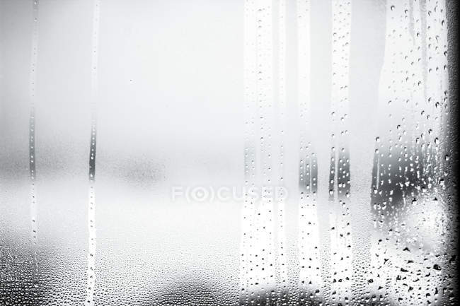 Closeup view of water drops on surface of window glass pane — Stock Photo
