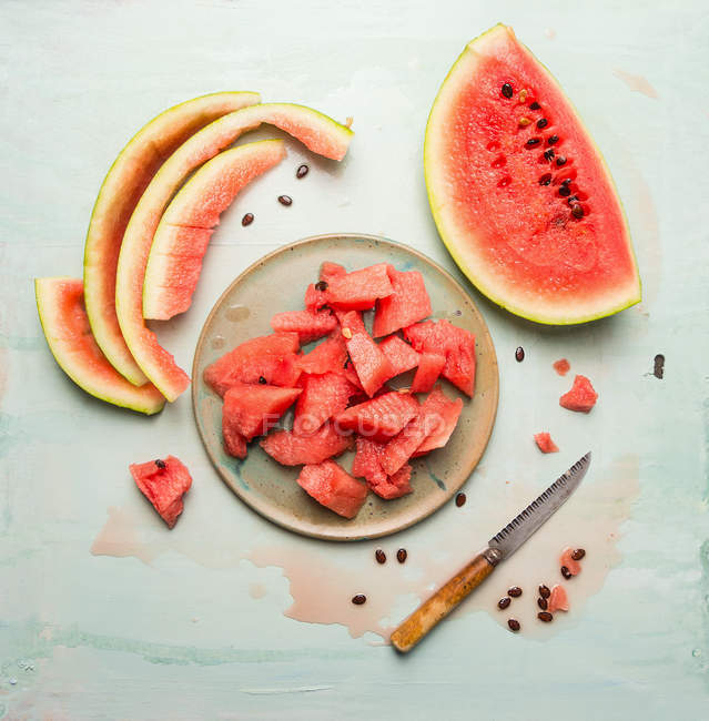 Sliced watermelon on plate with knife — Stock Photo
