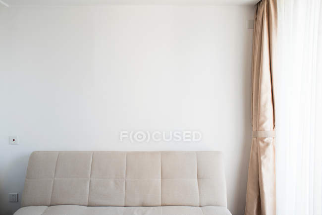 Room interior with sofa, white wall and curtain near window — Stock Photo
