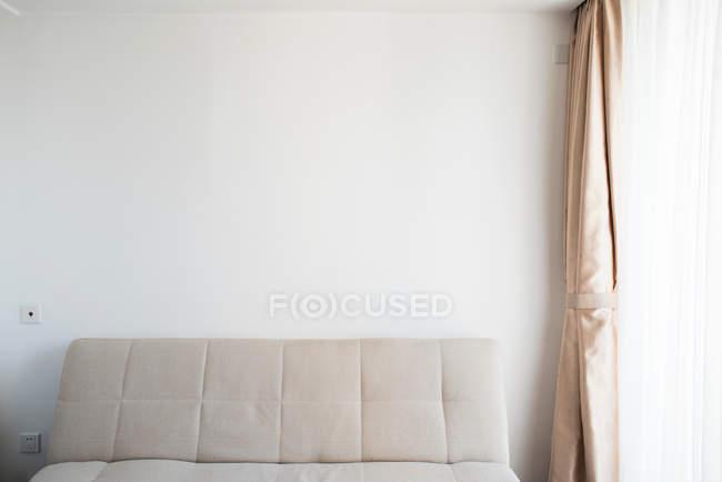 Interiore della stanza con divano, parete bianca e tenda vicino alla finestra — Foto stock
