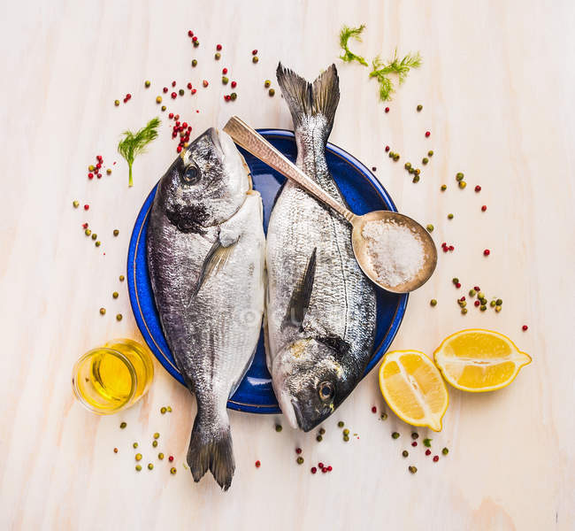 Raw fish with lemons and spices — Stock Photo