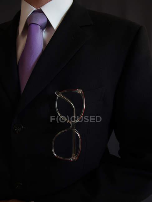 Eyeglasses in pocket of black male suit — Stock Photo