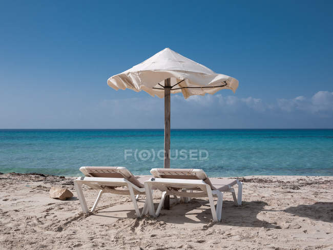 Шезлонги и зонтики на пляже с белым песком — стоковое фото