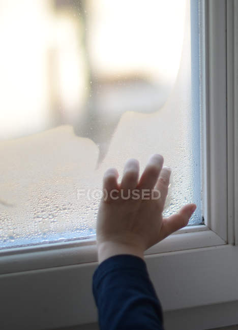 Close-up view of child hand drawing on wet window — Stock Photo