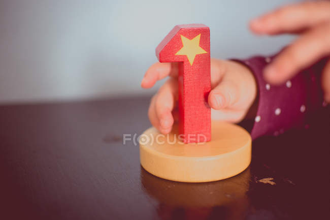 Close-up view of child hand holding digit toy — Stock Photo