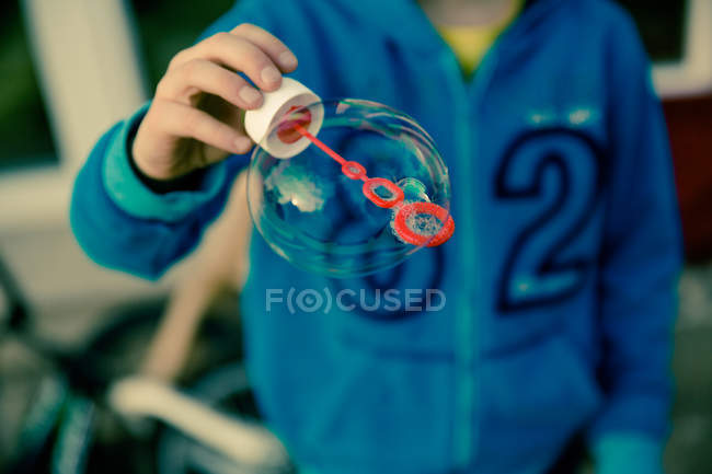Cropped image of child with soap bubble — Stock Photo