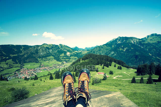 Botas contra montañas de verde verano - foto de stock