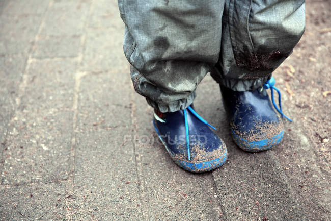 Close-up view of child feet in dirty rubber boots — Stock Photo