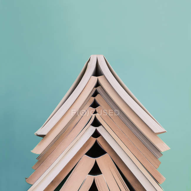 Closeup of books stacked on top of each other on turquoise background — Stock Photo