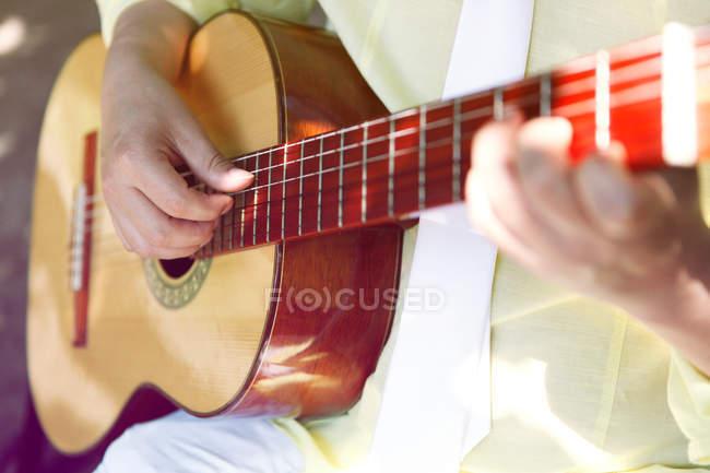 Vista parcial de cerca de guitarrista tocando la guitarra en sol - foto de stock