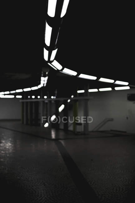 Lit lamps lines on black ceiling of underground space — Stock Photo