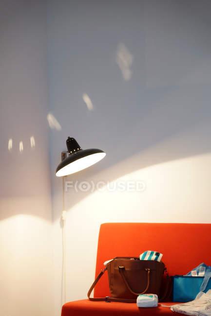 Сумочка и различные объекты на красный диван, Облегченный лампа в помещении — стоковое фото