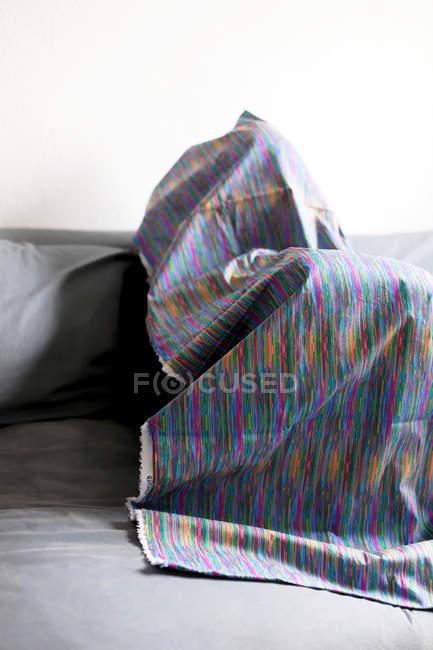 Figura umana coperto con un panno piegato sul sofà — Foto stock