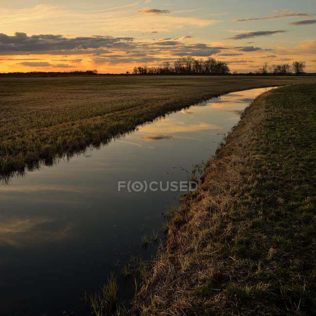 Vista panorâmica na paisagem com rio e pôr do sol reflexo — Fotografia de Stock