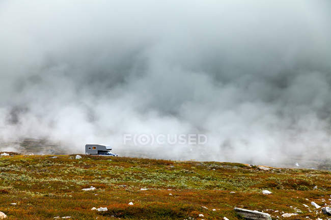 Mobile home on hill slope in fog — Stock Photo