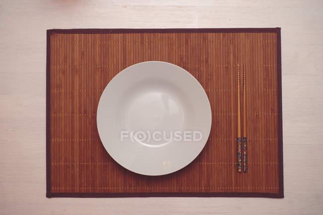 Un piatto bianco con le bacchette — Foto stock
