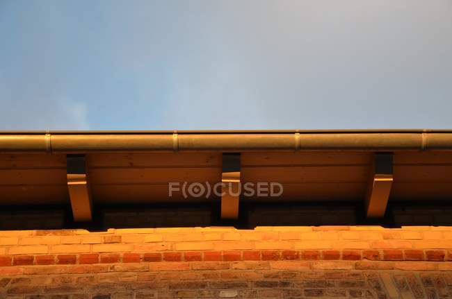 Eaves of house rooftop in sunset light — Stock Photo