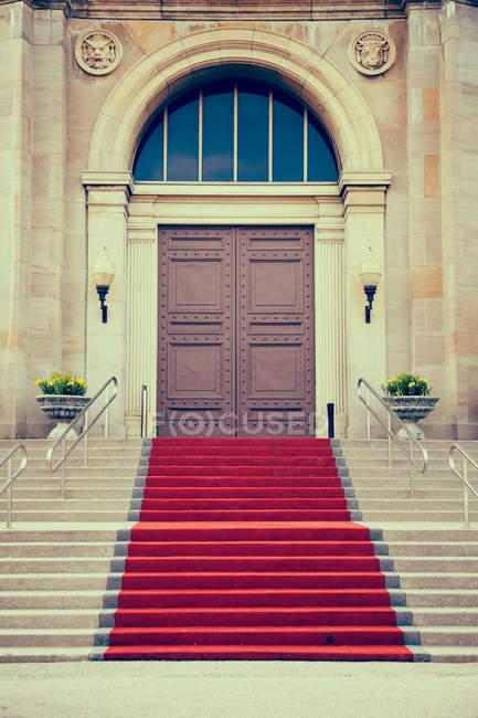 Iron doors and red carpet entrance with stone archway — Stock Photo