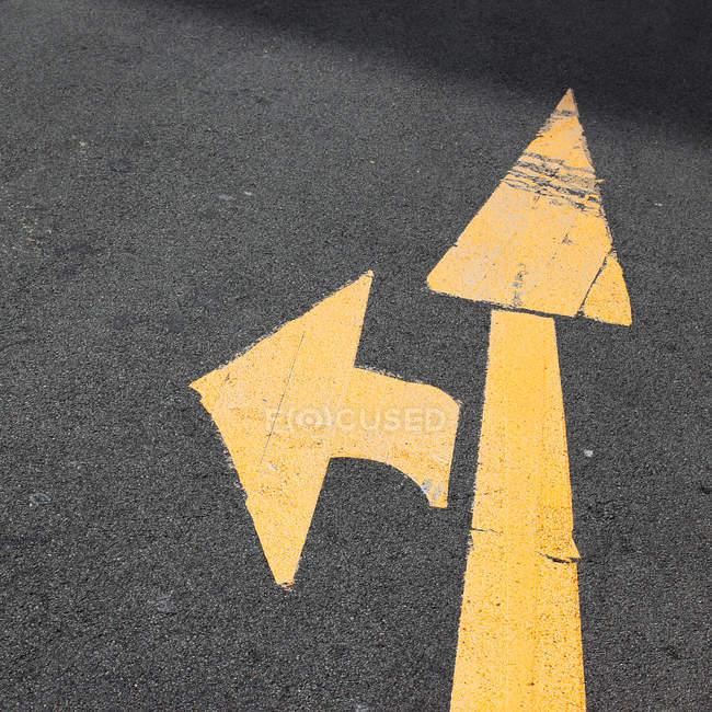 Vue rapprochée de la flèche signer sur l'asphalte — Photo de stock
