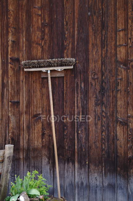 Broom hanging on brown wooden wall — Stock Photo