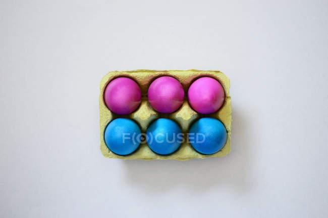 Eiern im Karton Tablett gemalt, blau und violett — Stockfoto