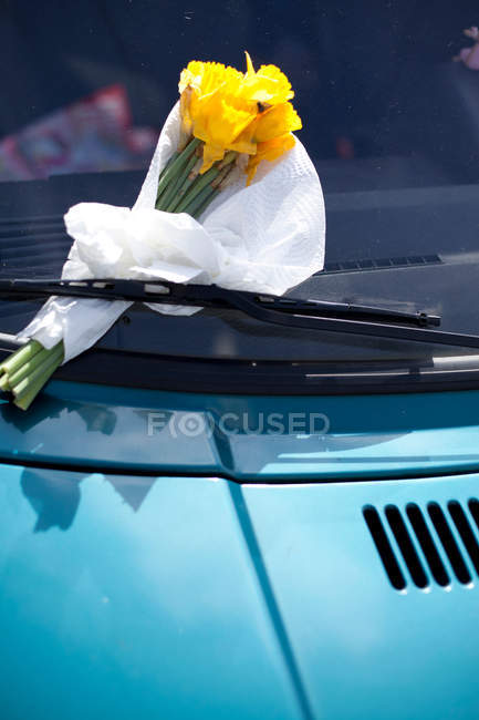 Daytime view of yellow flowers bouquet fixed in car windscreen wiper — Stock Photo