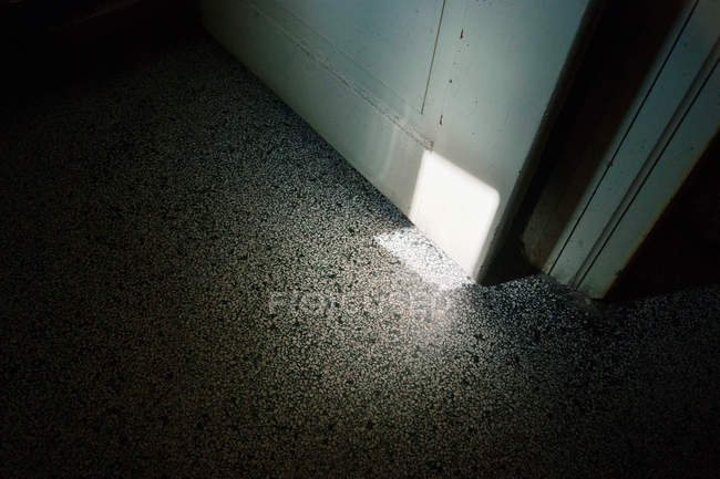Daytime view of rectangle light beam on stone floor and opened door — Stock Photo