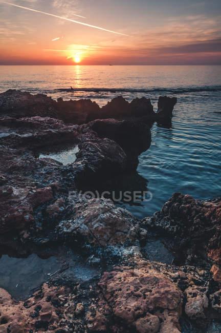 Vista distante da costa rochosa ao pôr do sol — Fotografia de Stock