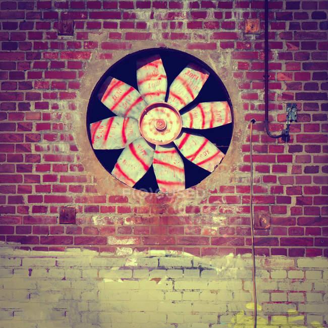 Close-up of fan on brick wall — Stock Photo