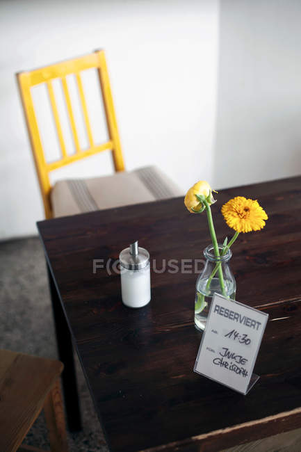 Daytime elevated view of flowers with sugar caster and reserved sign on wooden table — Stock Photo