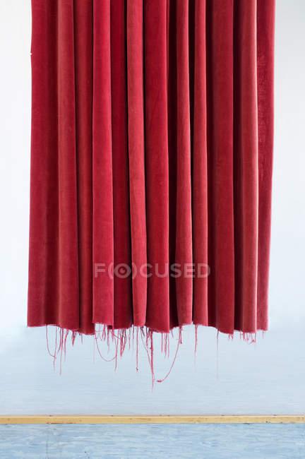 Detalle vista frontal de la cortina roja arrancó en pared blanca - foto de stock