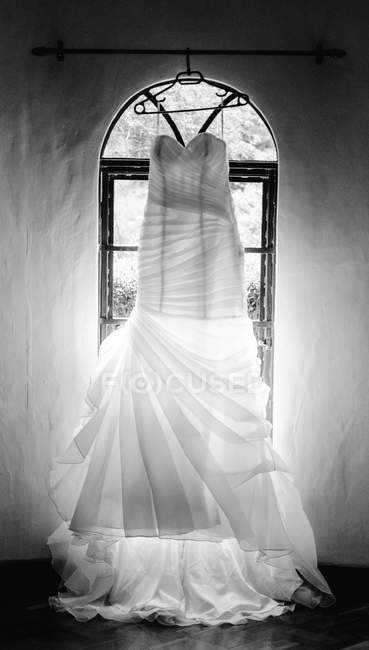 White wedding dress hanging on hanger in front of window — Stock Photo