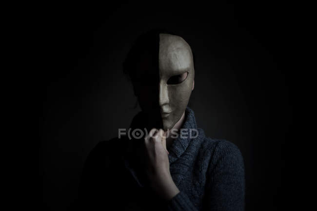 Person covering face with scary horror mask in dark room — Stock Photo