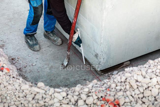 Обрезанный вид работника, измерения интервала в бетонной стене — стоковое фото