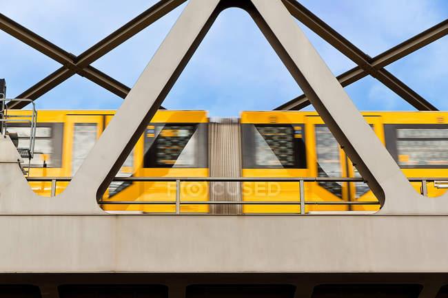 Brückenbau und gelber Zug in Bewegungsunschärfe — Stockfoto