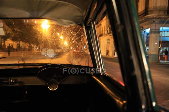 Closeup de exibição de detalhes interiores carro retrô com vidro frontal quebrado, rua no fundo da cidade de noite — Fotografia de Stock