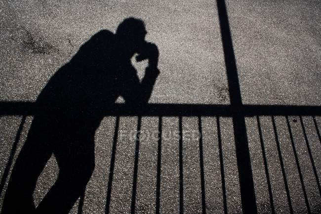 Shadows of man using mobile phone and railing on asphalt surface — Stock Photo