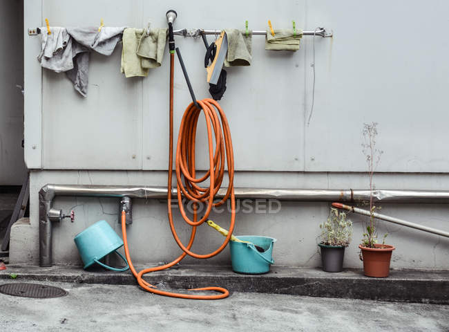Yard with buckets, metal pipe with taps and orange hose and rags — Stock Photo