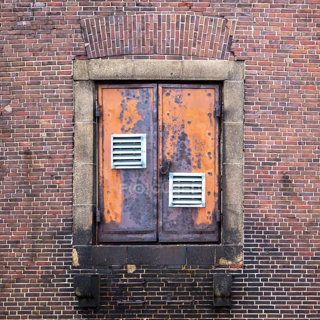 Bricks wall texture with rusty doors — Stock Photo