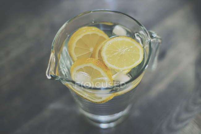 Zitronenscheiben mit Wasser im Glaskrug — Stockfoto