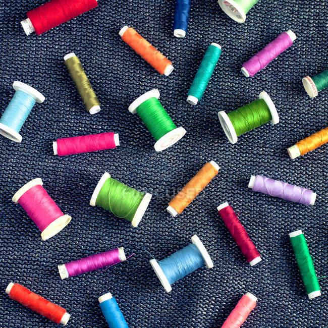Вид сверху различных красочных швейные катушки на поверхности ткани — стоковое фото