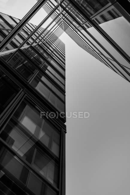 Vista inferior de fachada de cristal del rascacielos moderno - foto de stock