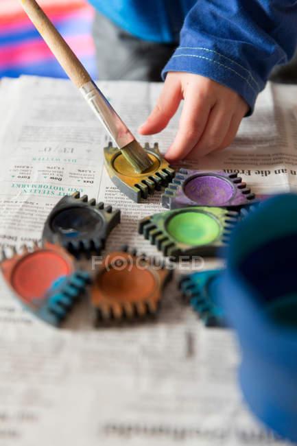 Main de l'enfant, de pinceau et de peintures colorées sur papier — Photo de stock