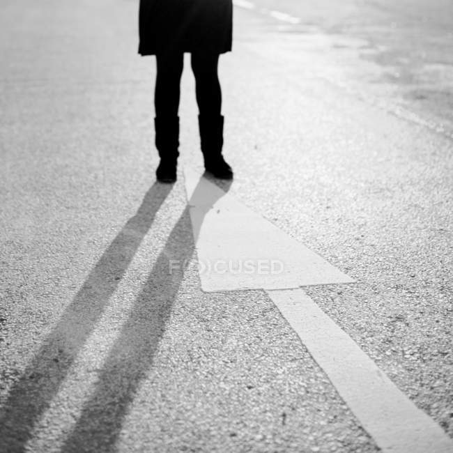 Cropped image of person legs standing on arrow sign painted on floor — Stock Photo