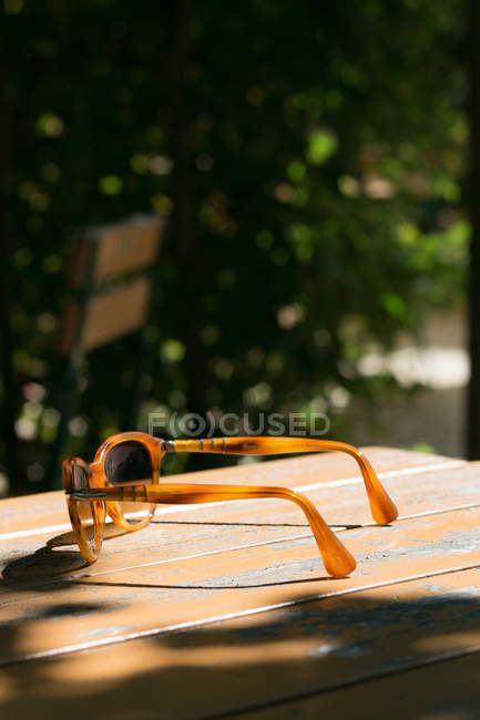 Sunglasses on wooden table in cafe — Stock Photo