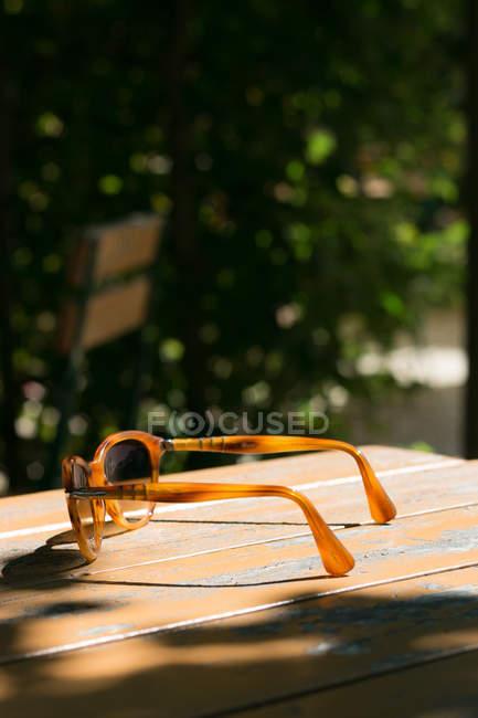 Sonnenbrille auf Holztisch im café — Stockfoto