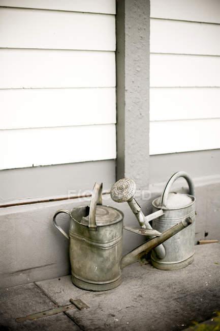 Tagsüber Blick auf zwei alte Gießkannen in der Nähe von Mauerbau — Stockfoto
