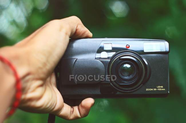 Hand holding analogue photo camera, green natural background — Stock Photo