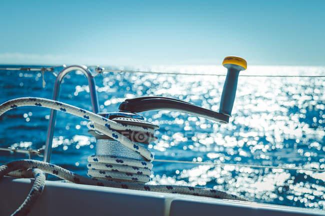 Vue de barre avec le câble sur le pont du voilier, un paysage ensoleillé sur fond — Photo de stock