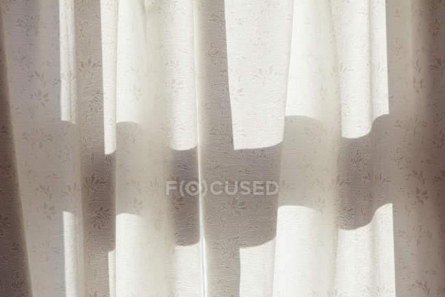 Blanco cortina sobre la ventana soleada - foto de stock